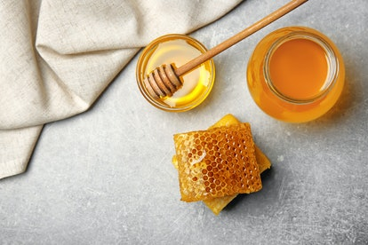 Delicious honey and fresh honeycombs on table, top view