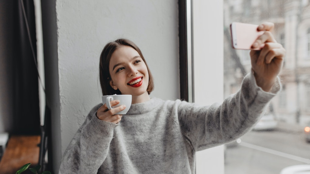 Picture of brown-eyed lady with red lipstick dressed in cashmere oversized outfit taking selfie with white cup of tea by window