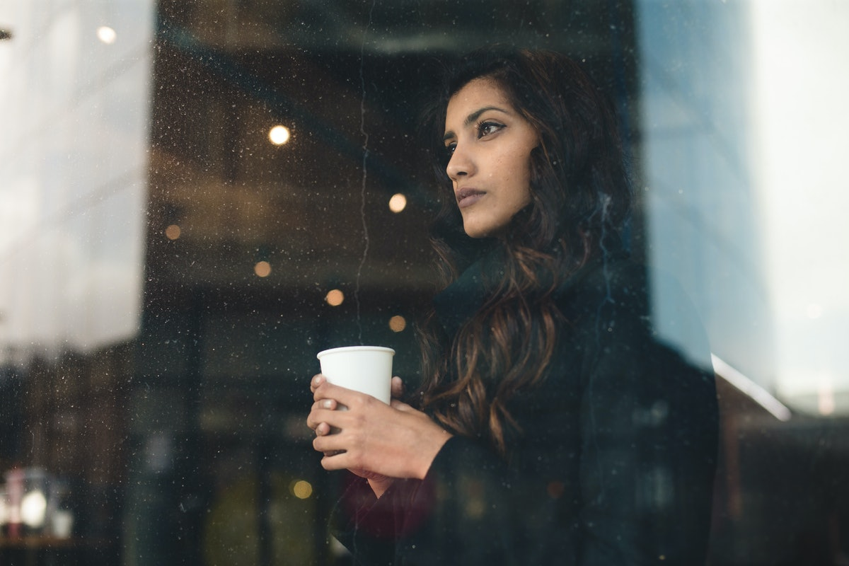 Young woman looking through rainy window