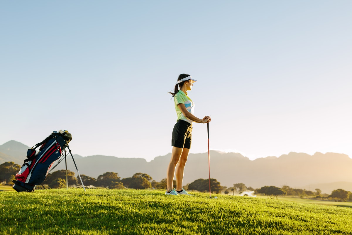 A woman looks out into the horizon on the golf course while holding a club.