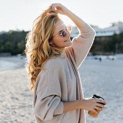 Stylish beautiful woman blonde in beige oversized sweater and brown sunglasses walks along beach wit...