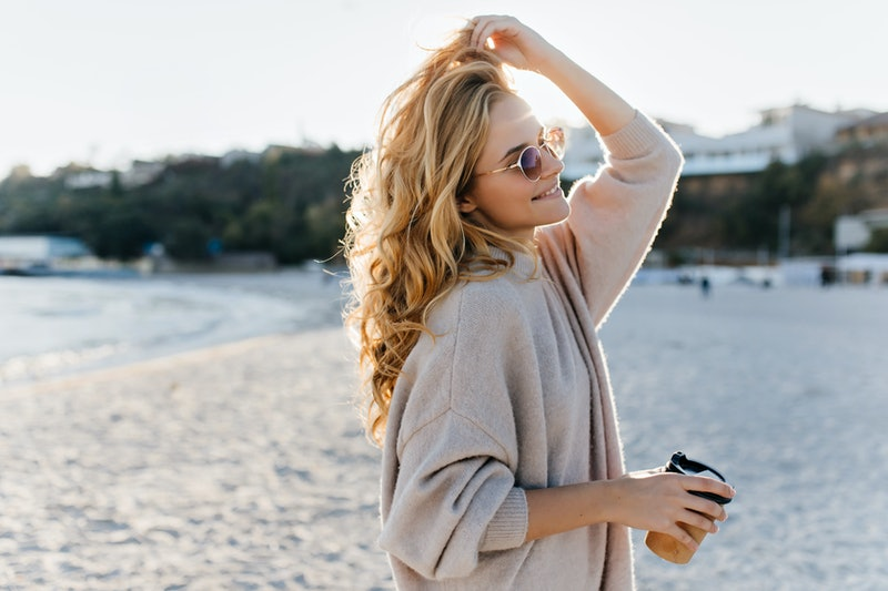 Stylish beautiful woman blonde in beige oversized sweater and brown sunglasses walks along beach with cardboard cup of tea