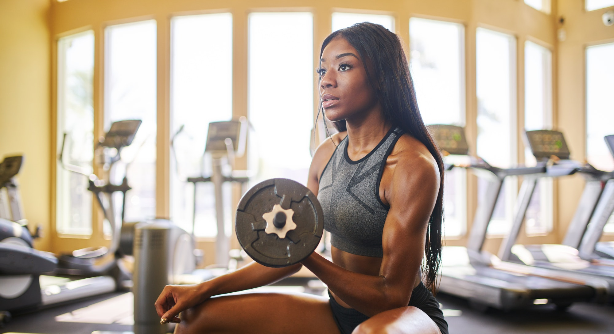 A person with braids sits on a bench in a gym and performs seated dumbbell curls. Dumbbell curls can be integrated into pretty much any workout.