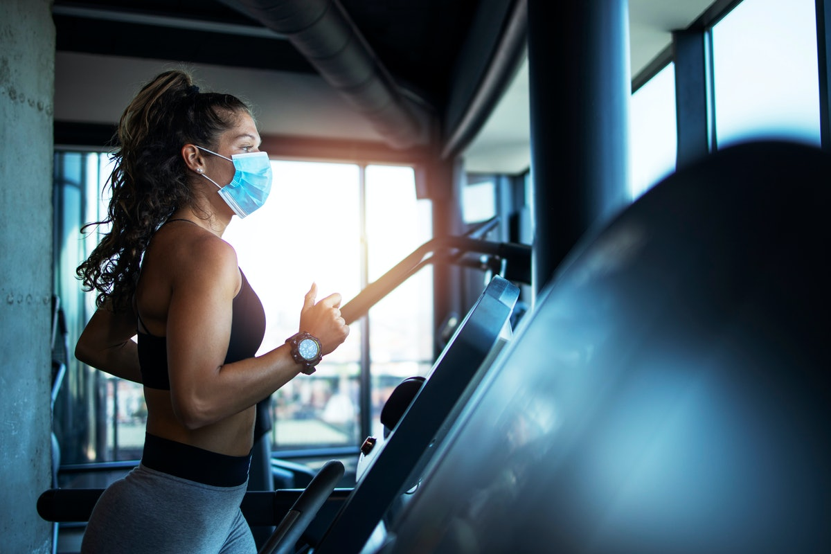 A person with a high ponytail wears a mask while running on a treadmill. Don't expect yourself to be able to sprint hard and fast just yet when you go back to the gym.