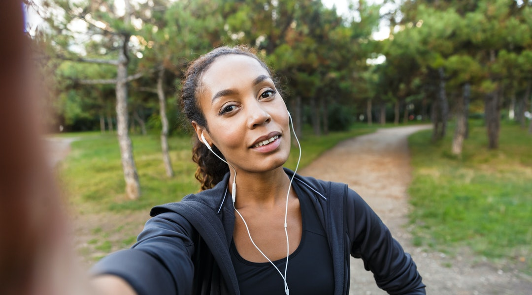 Portrait of pretty woman 20s wearing black tracksuit and earphones taking selfie photo on cell phone while walking through green park