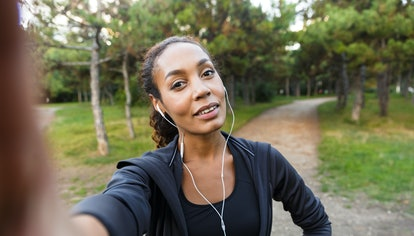 Portrait of pretty woman 20s wearing black tracksuit and earphones taking selfie photo on cell phone...
