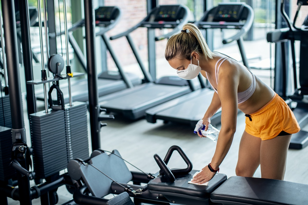 A blonde person wears a face mask while cleaning off a workout bench at the gym. Be mindful of where you're putting your stuff if you go to the gym during the pandemic.