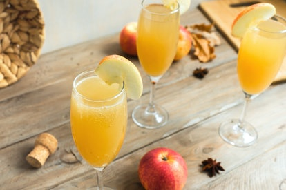 Apple Mimosa Cocktail in tall glasses and organic apples on wooden. Seasonal fall drinks for holiday - champagne mimosa cocktail with apples.