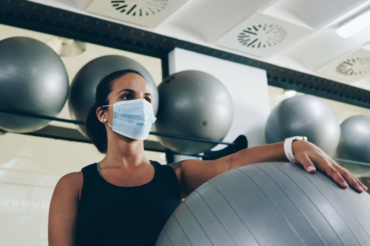 A person wearing a mask carries a yoga stability ball with one arm in the gym. It might be tough, but it's best not to hug your gym buddies for now.