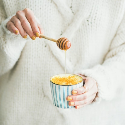 Healthy vegan turmeric latte or golden milk with honey in female hands, square crop