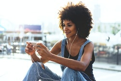 An attractive young dark-skinned girl looking at video on mobile phone while relaxing outside in summer warm day. young girl with afro hair playing in a game on the cellphone. girl  watching videos