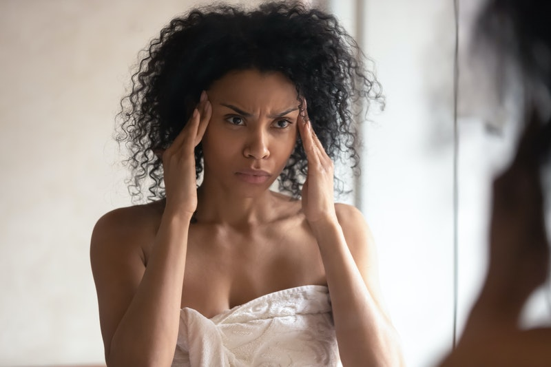 Thoughtful african American woman look in mirror in bathroom worry about facial wrinkles think of anti-aging treatment procedure, biracial female have skin problems, cosmetologist help, beauty concept
