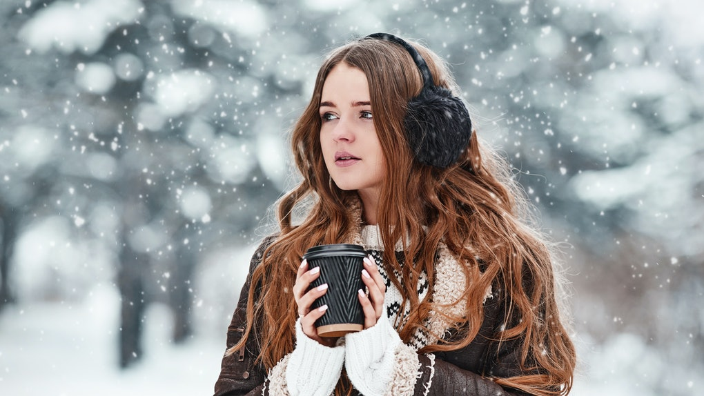 Happy young woman with cup of coffee in snowy winter day. Girl enjoys winter, frosty day. Walk in winter forest.