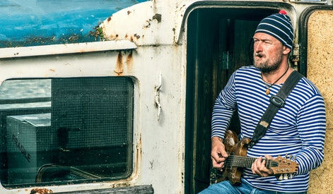 Old salt man playing guitar on his rusted ship
