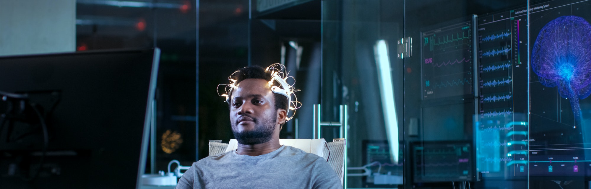 Man Wearing Brainwave Scanning Headset Sits in a Chair while Watching Stimulating Images on Display at Night. In the Modern Brain Study Laboratory Monitors Show EEG Reading and Brain Model.