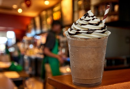 Cup of iced medium coffee or Frappuccino with cream and chocolate sauce on wooden counter at cafe.