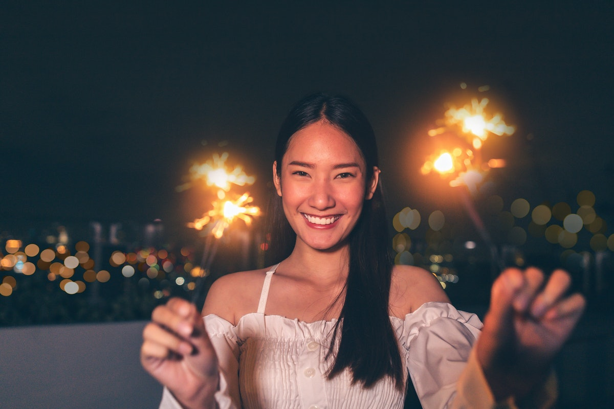 Beautiful young asian brunette woman with white dress joying Christmas or New Year night on a city.W...