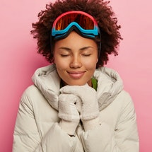 Feeling reaxed and happy. Healthy adorable woman with curly hair, wears white down padded coat and mittens, uses ski mask for favourite hobby, eyes shut. Woman snowboarder recreats during winter