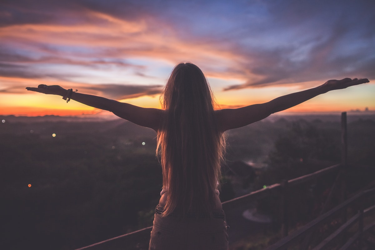 Silhouette of the woman spreading arms and standing high on the viewpoint with breathtaking view ove...