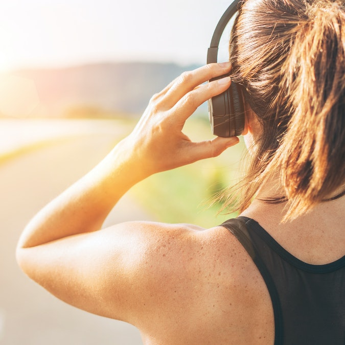 Close up image of teenager adjusting  wireless headphones before starting jogging and listening to music