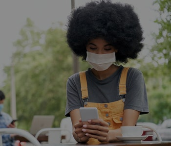 African American young hipster gen z female with Afro hair wearing face mask holding smart phone using mobile apps sitting at table in outdoor cafe. Social distancing everyday life and tech concept