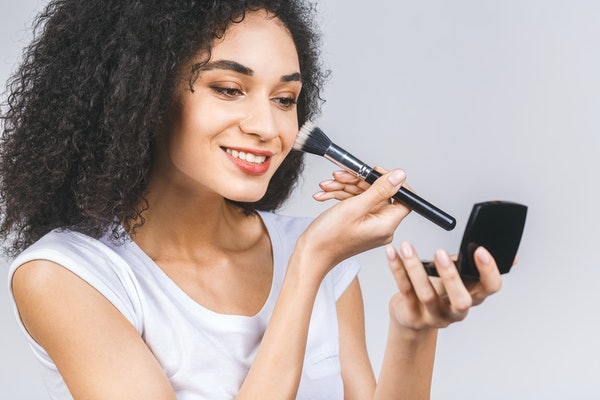 Smiling afro american woman applying makeup powder or foundation with brush isolated on a grey background.