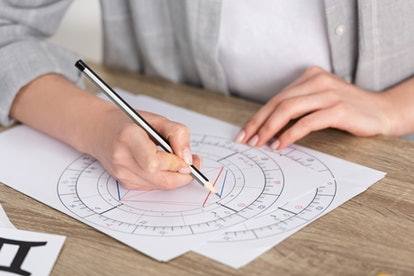 Cropped view of astrologer drawing natal chart on wooden table