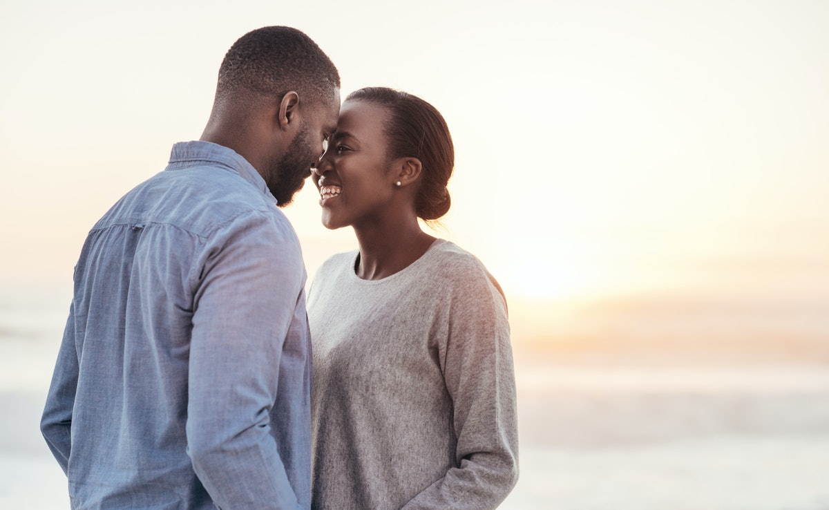 Smiling young African couple talking and laughing together while standing face to face on a beach at...