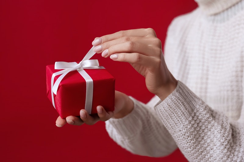 Female hands open Christmas red gift box with white bow on the red background. White sweater. New Year concept. Winter holidays and presents. Surprise delivery. Unpacking. Valentine's day, Birthday