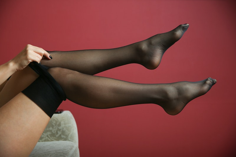woman putting on sheer black tights close up