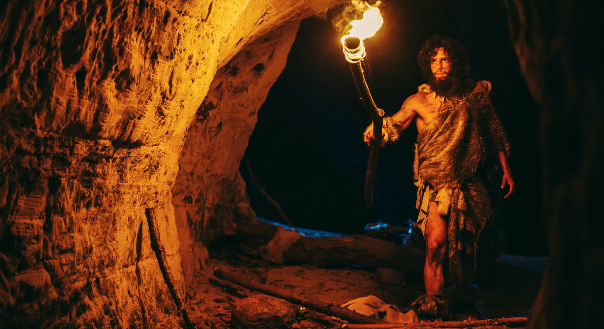 Primeval Caveman Wearing Animal Skin Exploring Cave At Night, Holding Torch with Fire Looking at Dra...