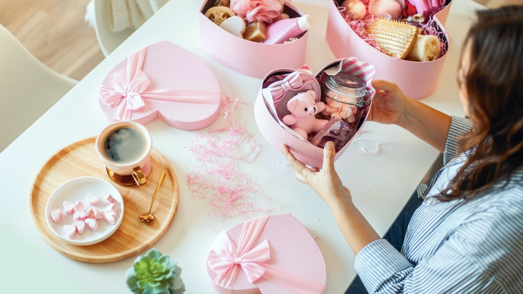 A woman prepares a pink heart-shaped gift basket with a teddy bear and products for her friend on Valentine's day.