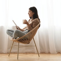 Free time. Girl using tablet and drinking coffee, sitting in wicker chair against window, panorama with free space
