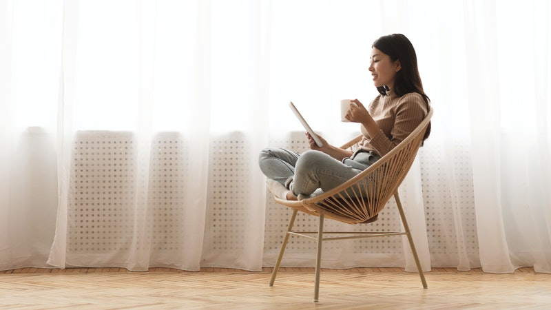 Free time. Girl using tablet and drinking coffee, sitting in wicker chair against window, panorama w...