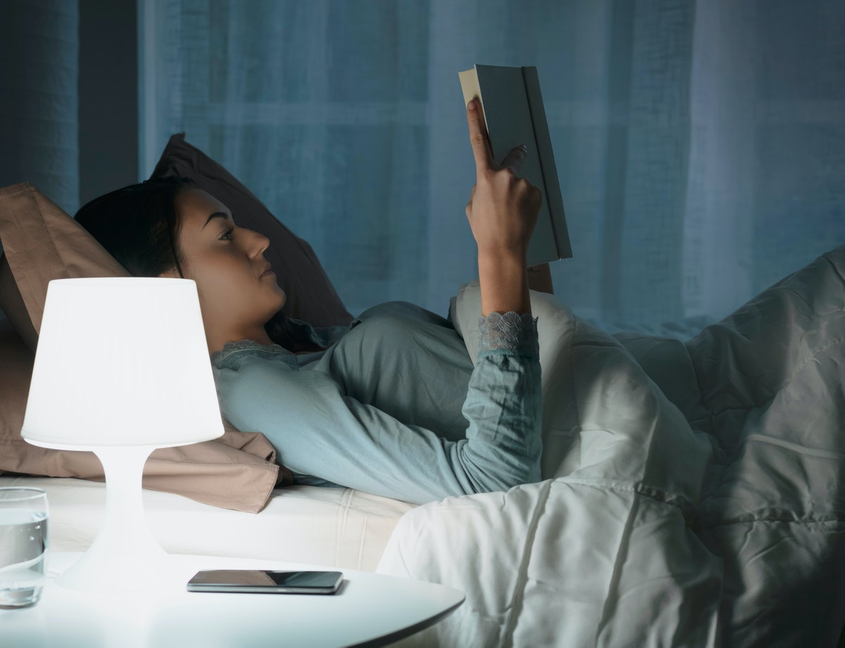 Young beautiful woman lying in bed and reading a book late at night