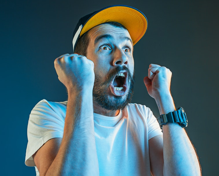 The anger and screaming man. Hate, rage. Crying emotional angry man in colorful bright lights at studio background. Emotional face. Fan human emotions, facial expression concept.