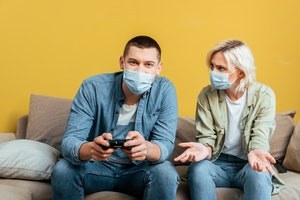 KYIV, UKRAINE - APRIL 22, 2020: young man in medical mask playing video games with displeased girlfriend on sofa near yellow wall