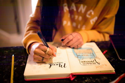 Closeup of young teen girl writing in bullet journal on mood tracker page