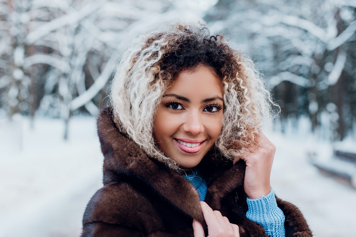 Smiling afro american girl wearing in fur coat in winter park