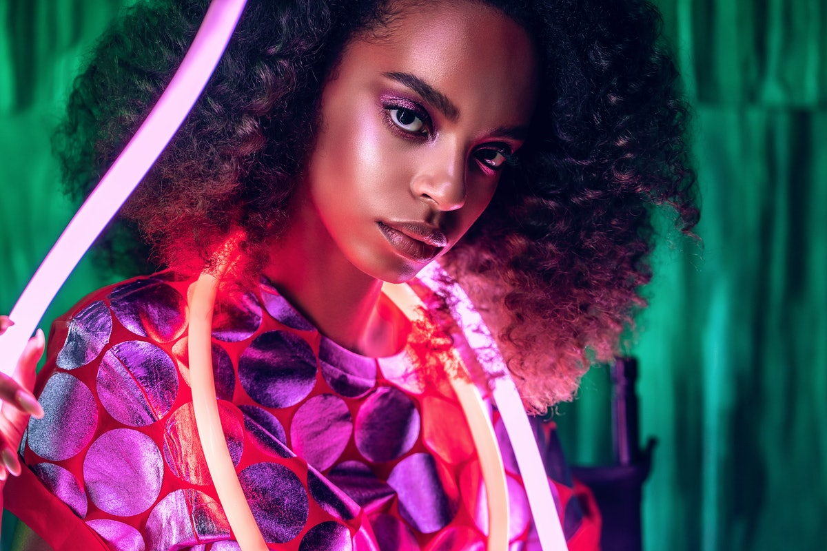 Portrait of african girl in pink top with pink neon light. Woman with afro hairstyle. Pink and red flexible neon light tubes