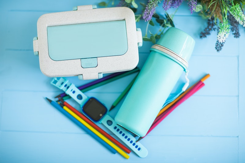 Back to school concept. Lunch box, watch, and blue thermos isolated on blue. Close up photo. Focus at smart watches for children with lunch boxes. Food concept.