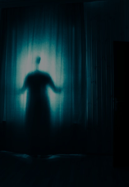 Horror silhouette in window with curtain inside bedroom at night. Horror scene. Halloween concept. B...