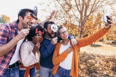 Group of young people hangout in the park.They are make selfie photo with halloween props.