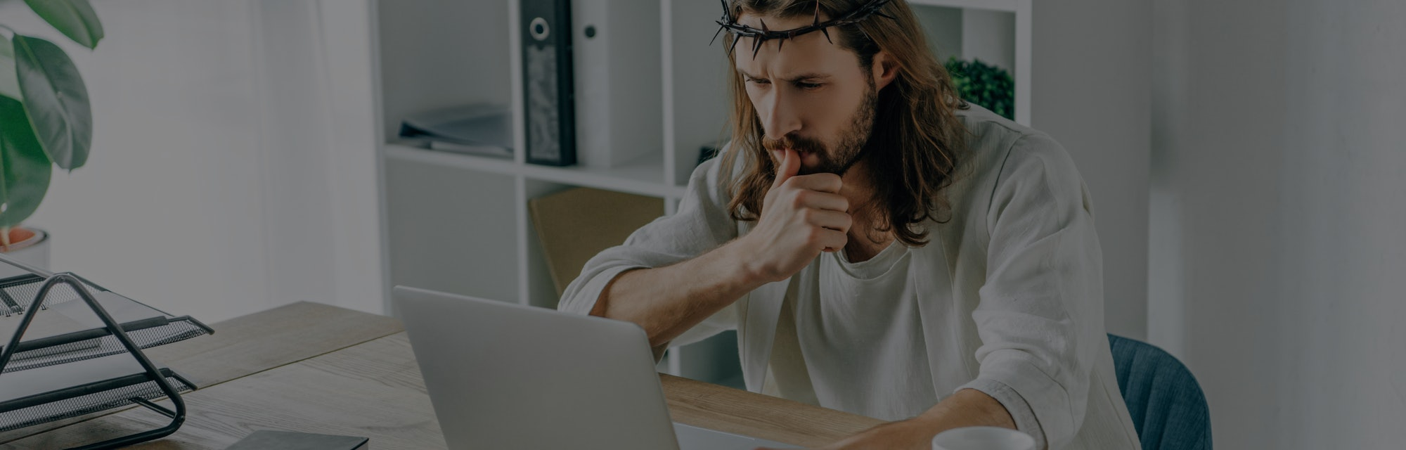 pensive Jesus in crown of thorns using laptop at table in modern office