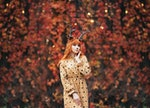 woman with deer makeup and horns in autumn forest during halloween
