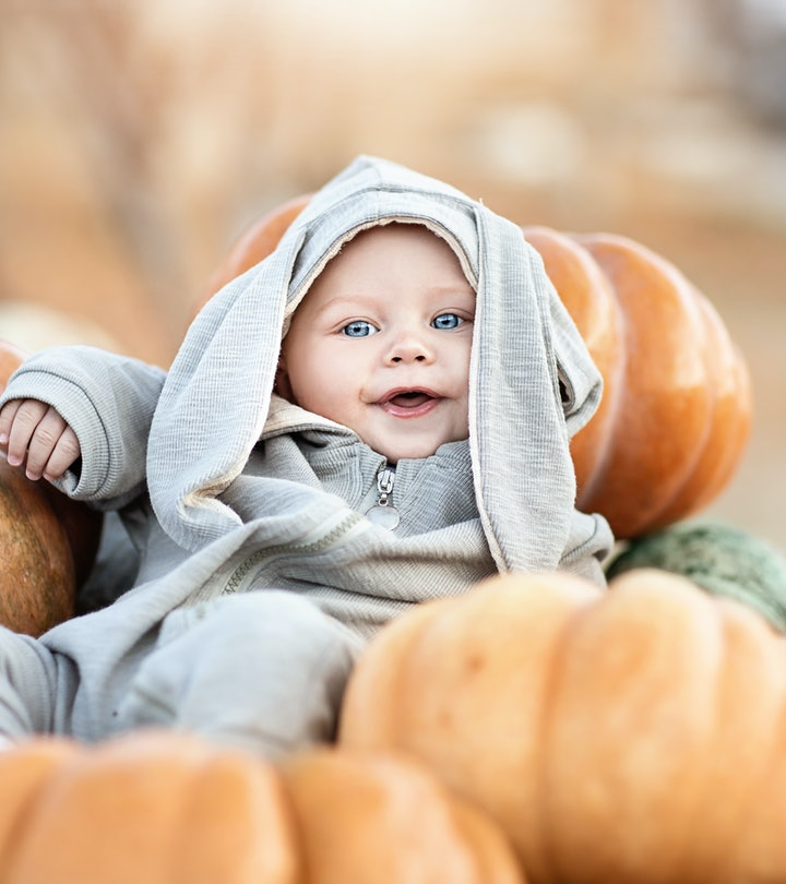 Cute little baby boy in a Bunny costume among a crop of pumpkins.