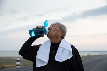 Close up Asian elderly drink water after exercise In the morning. health lifestyle and exercise Conc...
