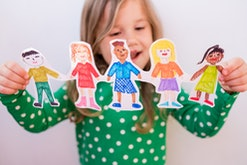 Close-up kid girl holding paper homemade garland with painted children of different races. Happy  in...