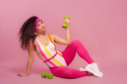 Beautiful brunette girl, curly hair, doing exercise in 80s fitness fashion style in studio isolated ...