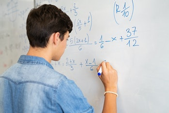 Back view of high school student solving math problem on whiteboard in classroom. Young man writing ...